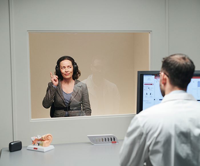 Hearing care professional testing a patient's hearing.