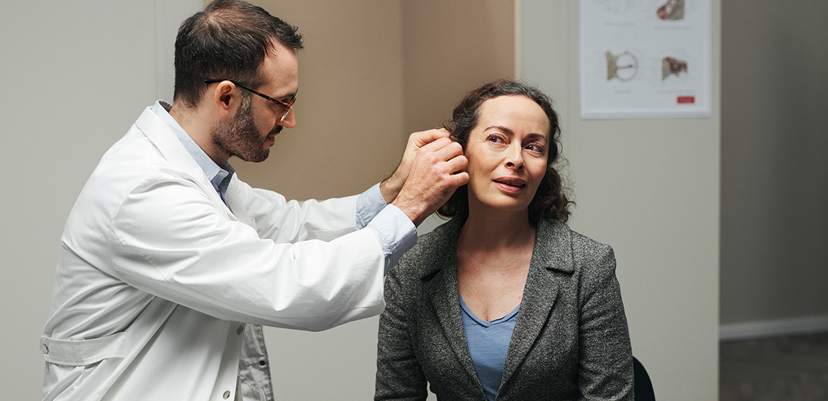 Audiologist fitting a ReSound hearing aids user.