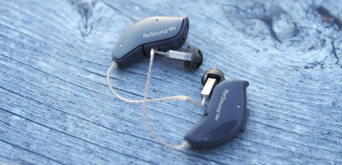 Small pair of ReSound hearing aids on a table.