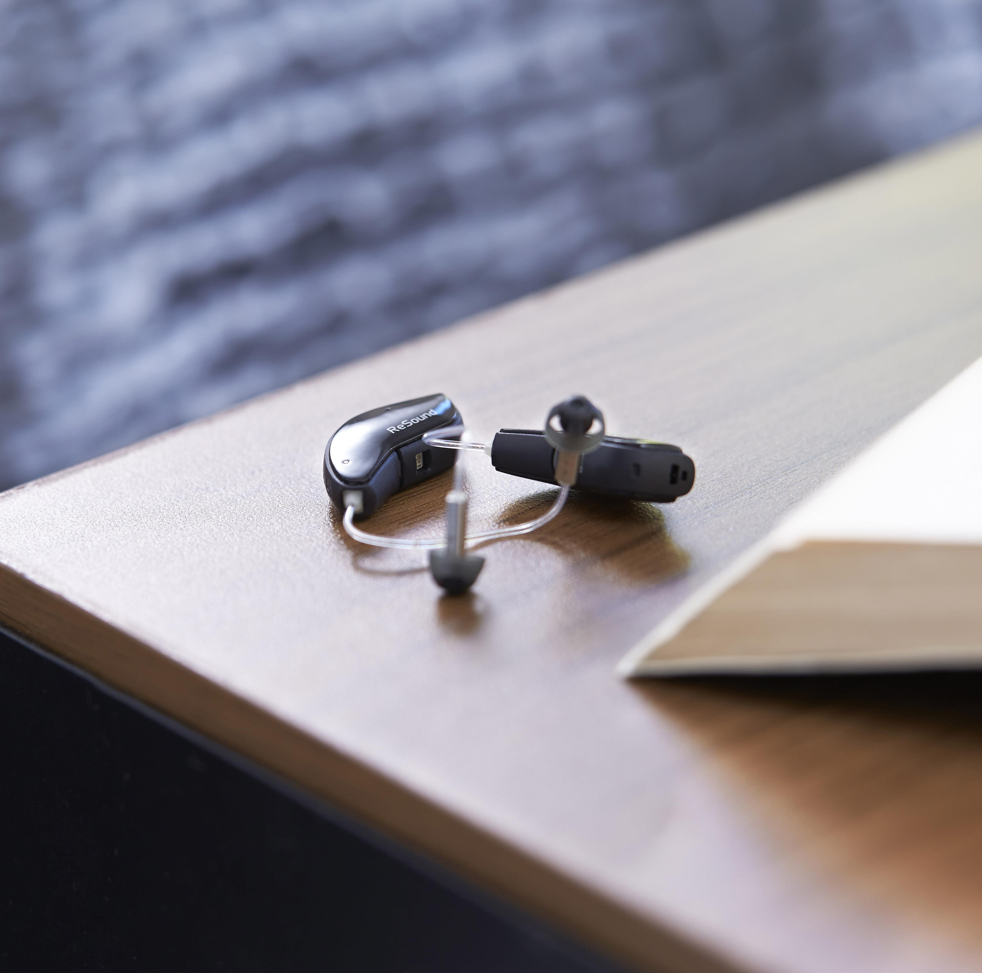 Pair of ReSound  hearing aids on a table.
