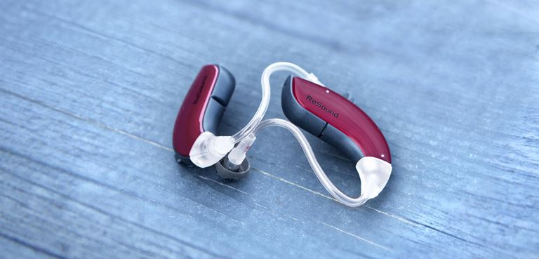 Pair of ReSound red hearing aids on a table.