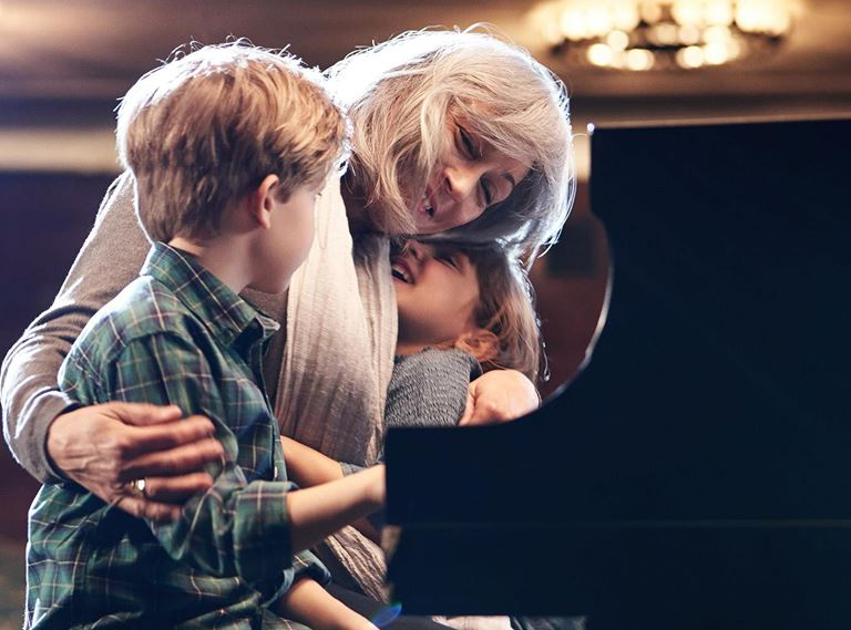 Woman playing piano with grandkids wearing LiNX Quattro hearing aids